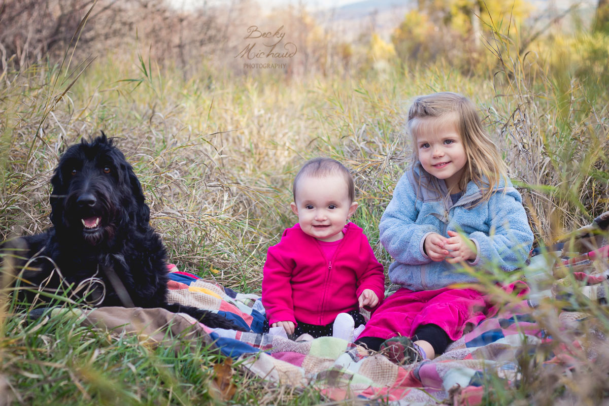 Young girls sitting with their dog on a blanket in Colorado