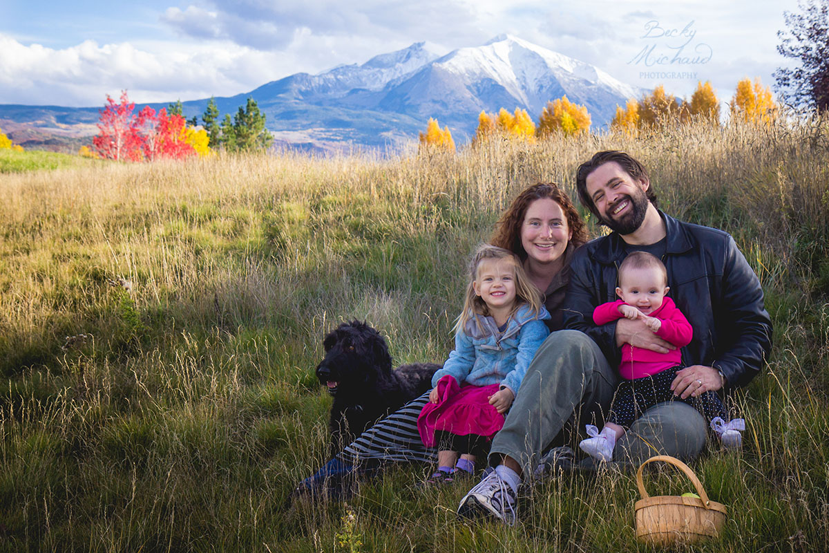 Family of four in a field in the Colorado mountains