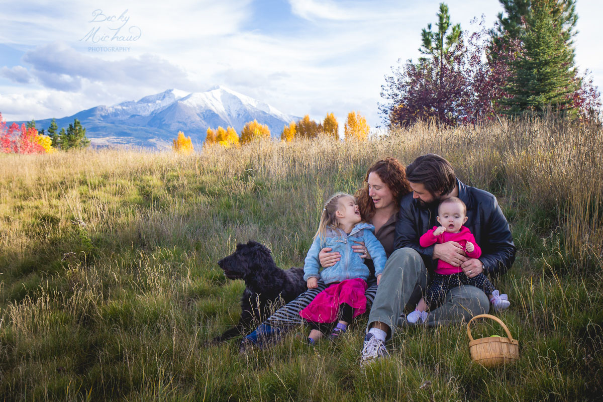 Family in a grassy field with mountain the background