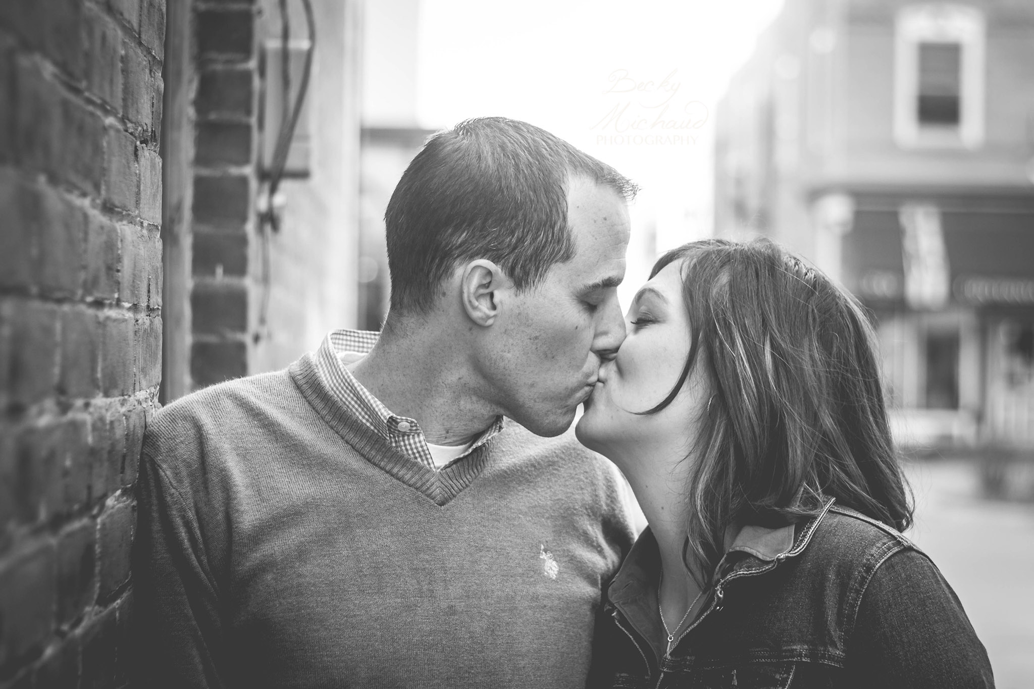 black and white photo of couple kissing by brick wall in Old Town Fort Collins