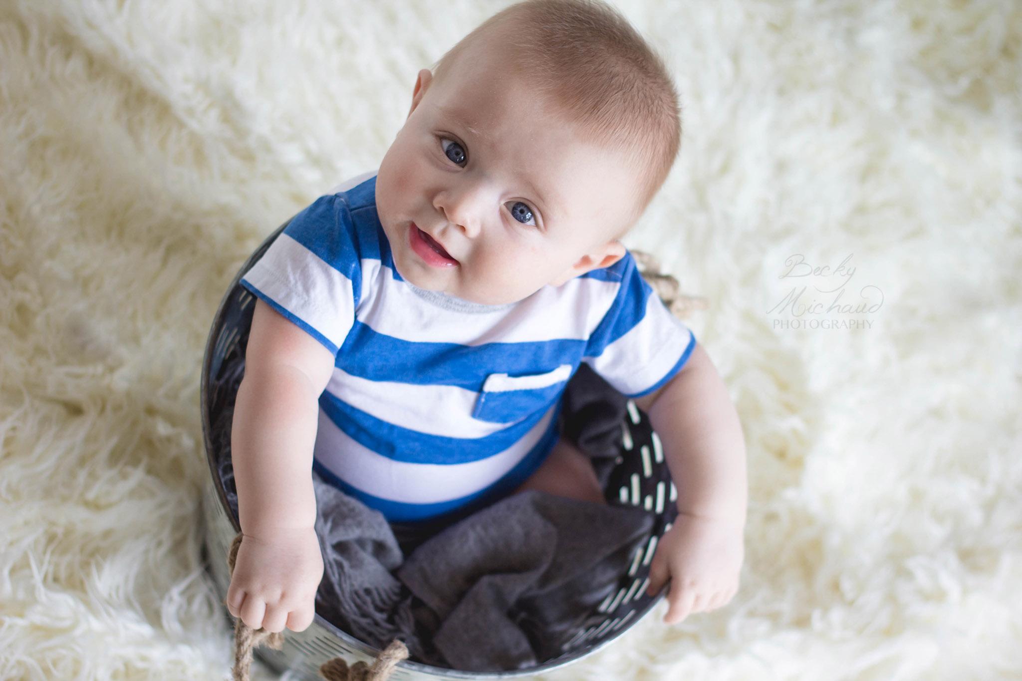 Baby boy wearing a striped blue shirt sitting in a bucket