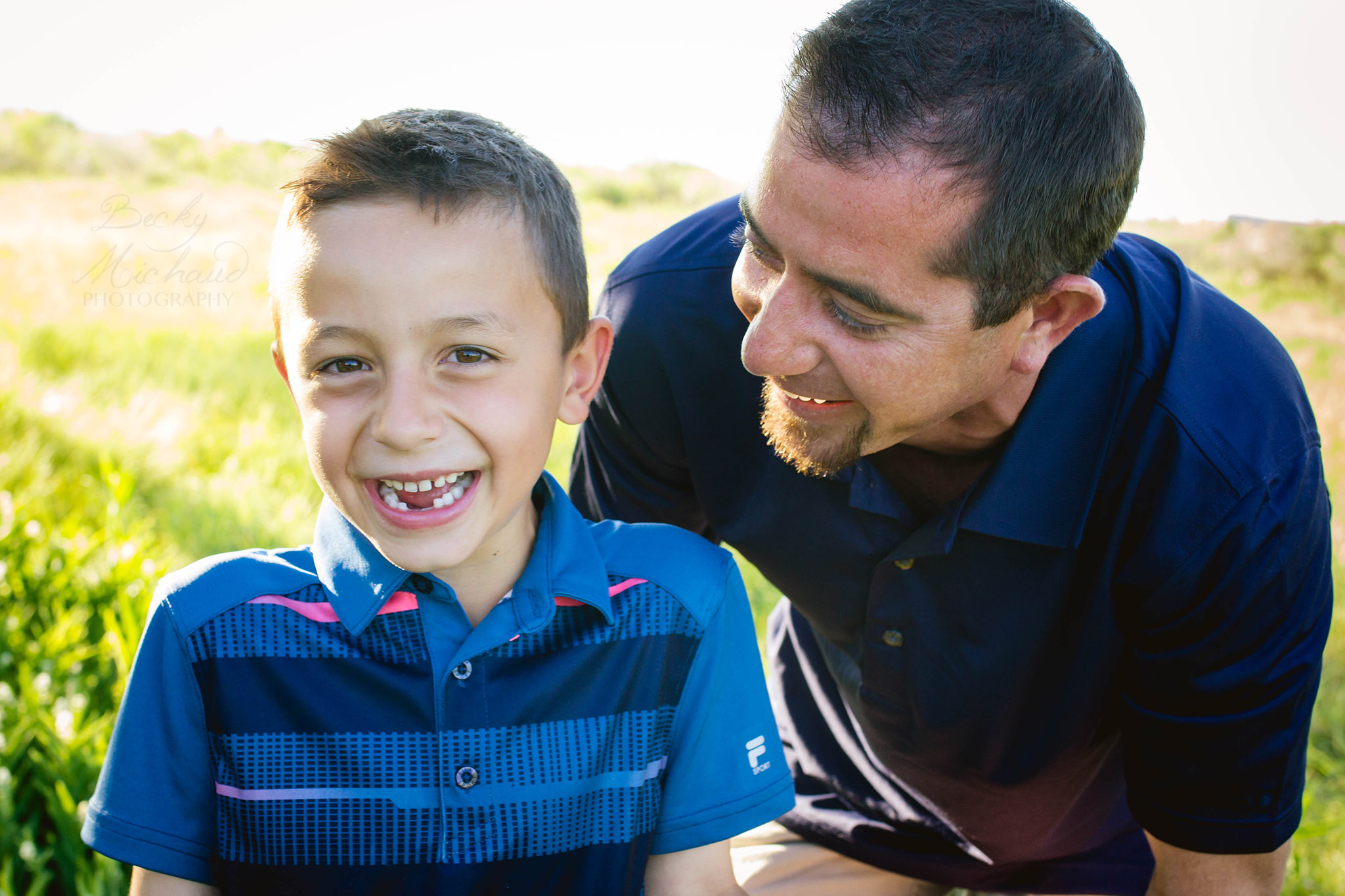A boy and his father laughing in a field in Loveland Colorado