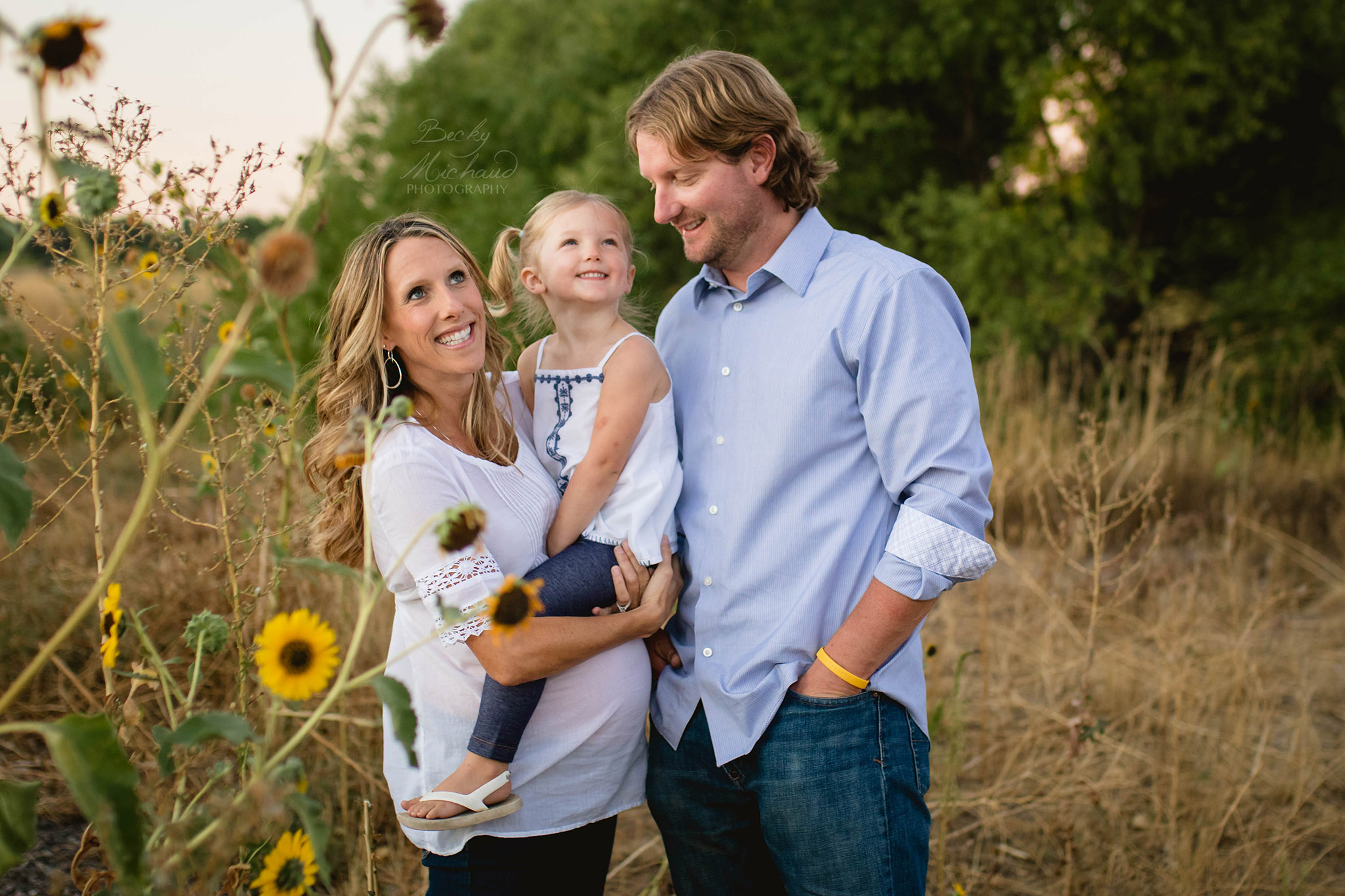 family of three in a field of sunflowers in south Fort Collins