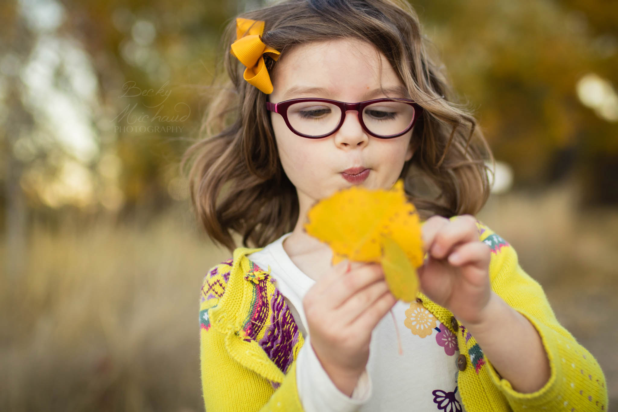 Lifestyle portrait of a little girl examining a yellow leaf during her fall family photos