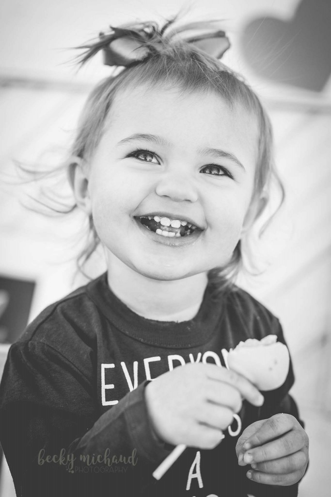Black and white photo of a girl eating a cake pop taken by Becky Michaud, Northern Colorado Photographer