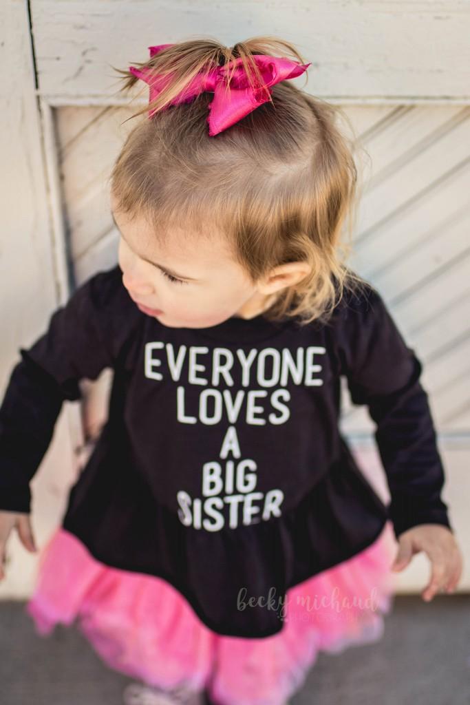 A girl wearing a big sister shirt