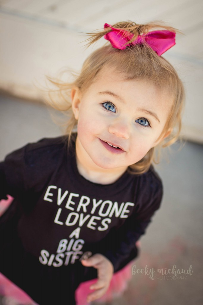 Portrait of a little girl wearing a big sister shirt taken by Becky Michaud, Fort Collins Photographer