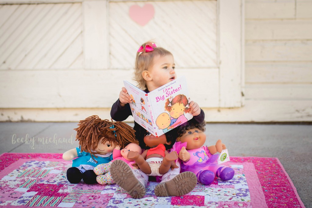 A little girl reads a book to her dolls