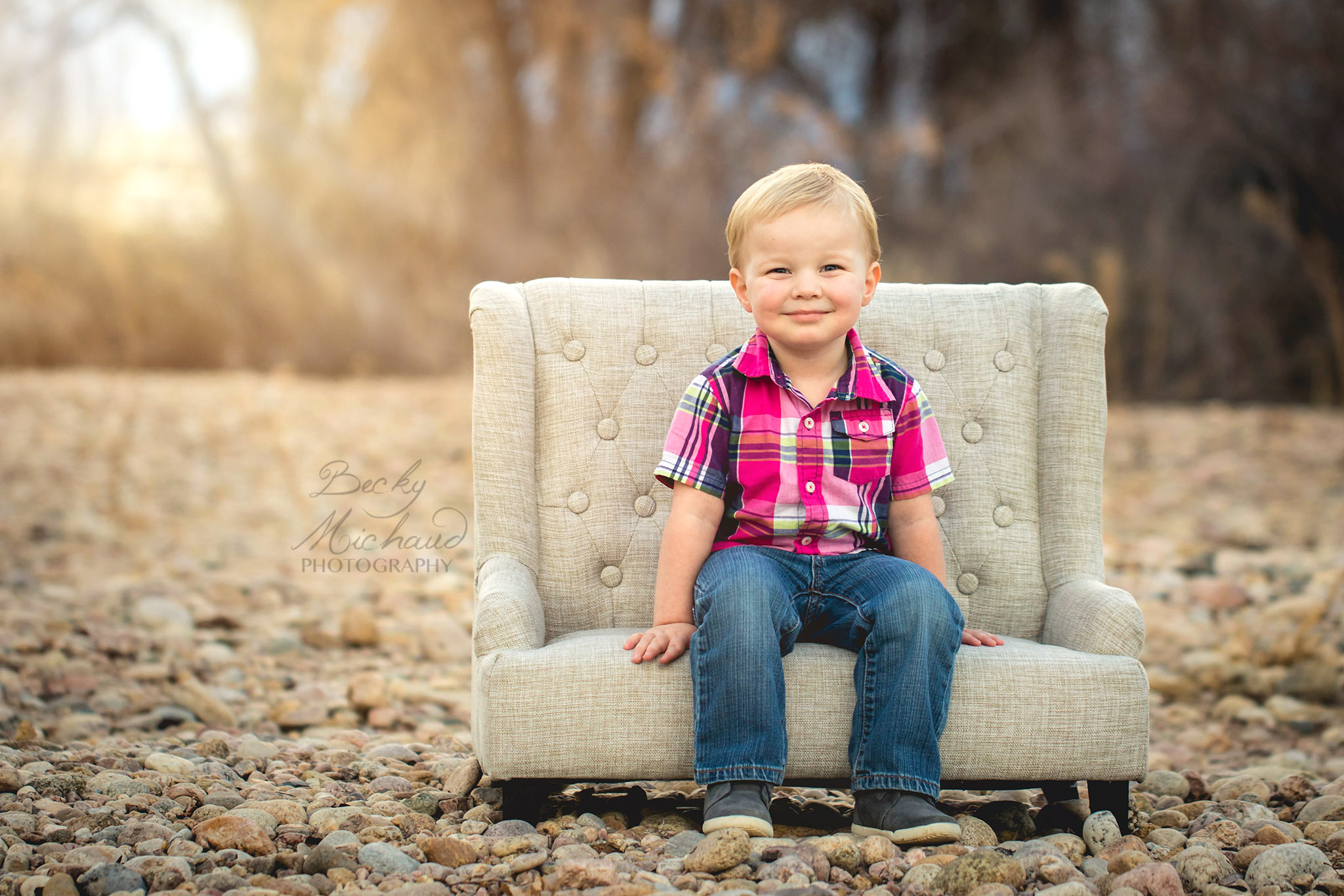 A toddler sits on a small white couch in a field of river rock