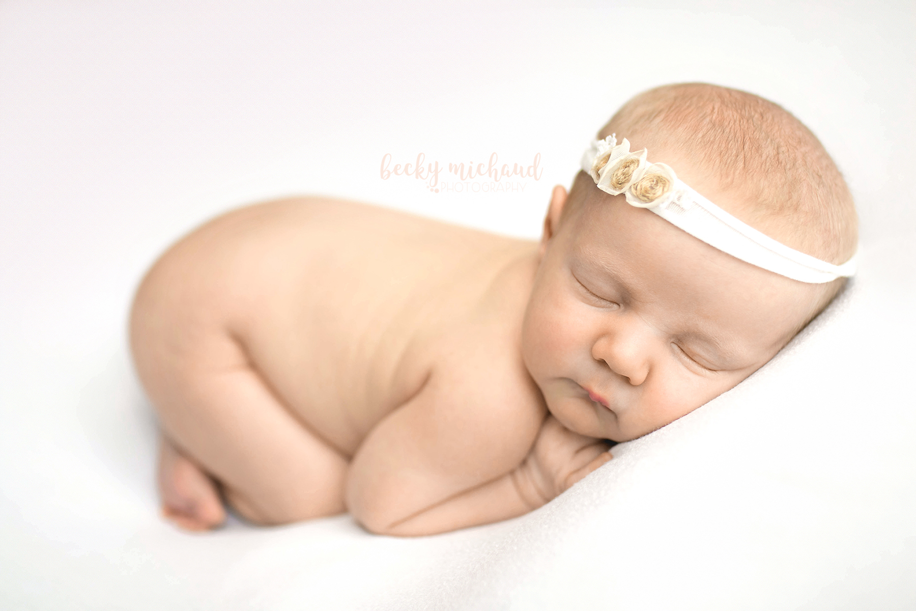 baby girl wearing white floral headband on a white backdrop in Northern Colorado