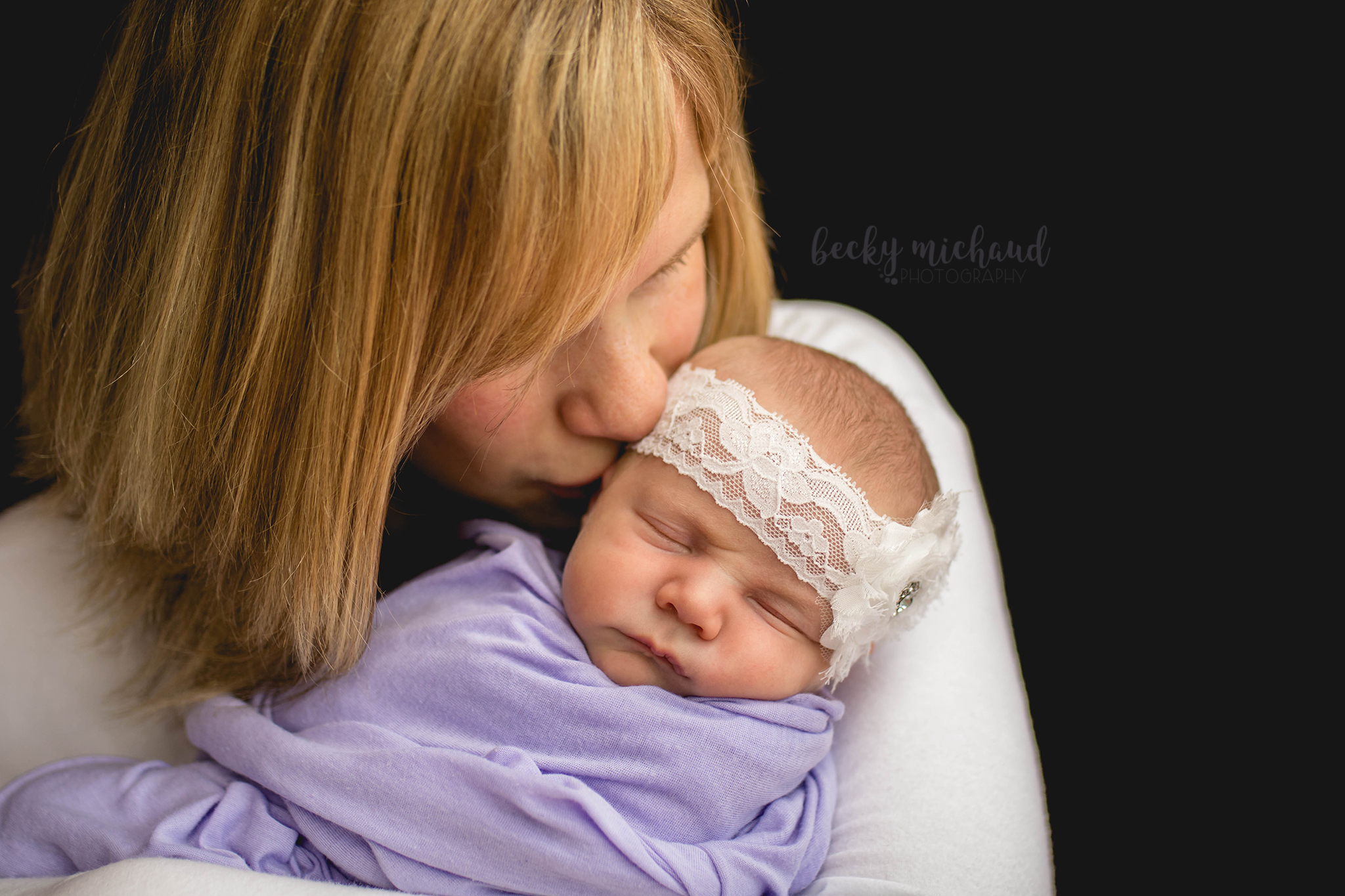 a mother kisses her new baby girl