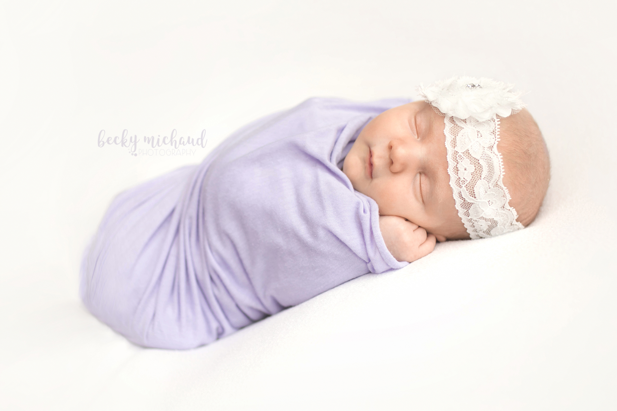 baby girl in a purple wrap on a white background