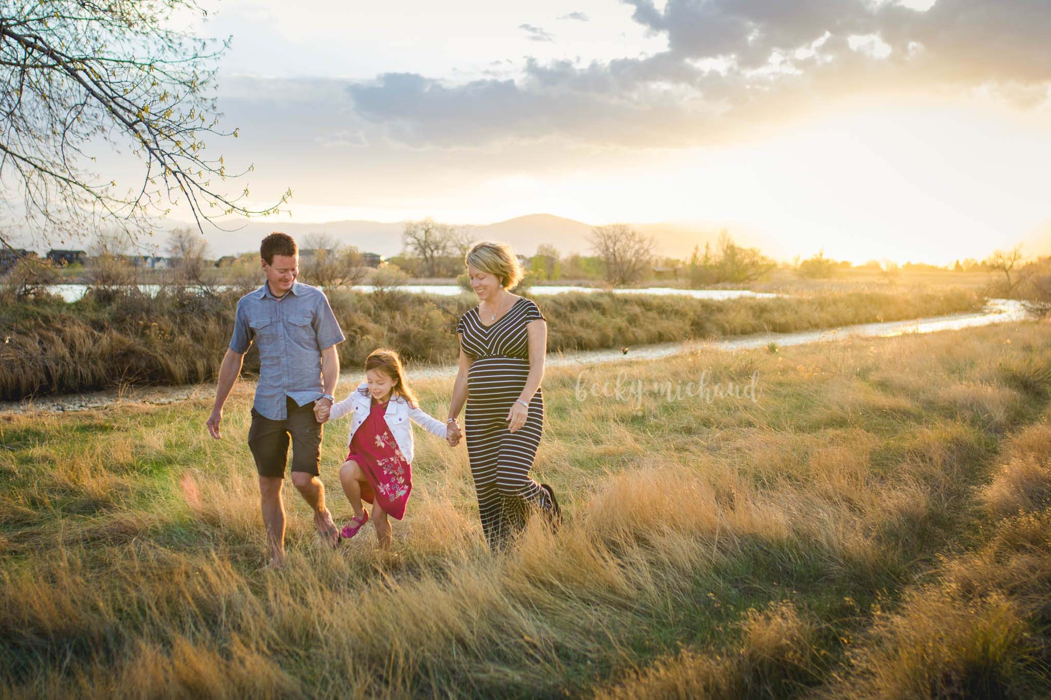 A couple walks through a field with their little girl and a baby on the way
