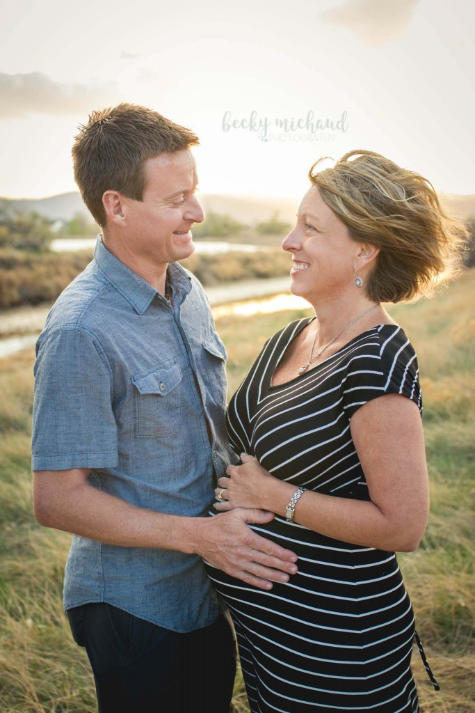 A couple poses for their maternity photo session at sunset