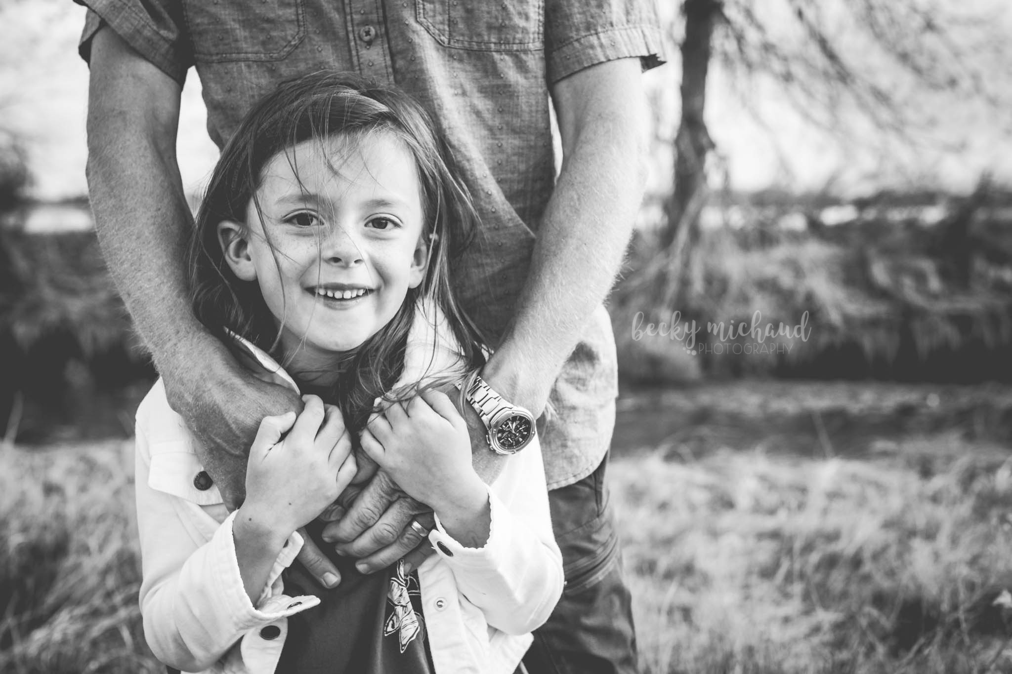 A young girl holds her dad's hands while he hugs her