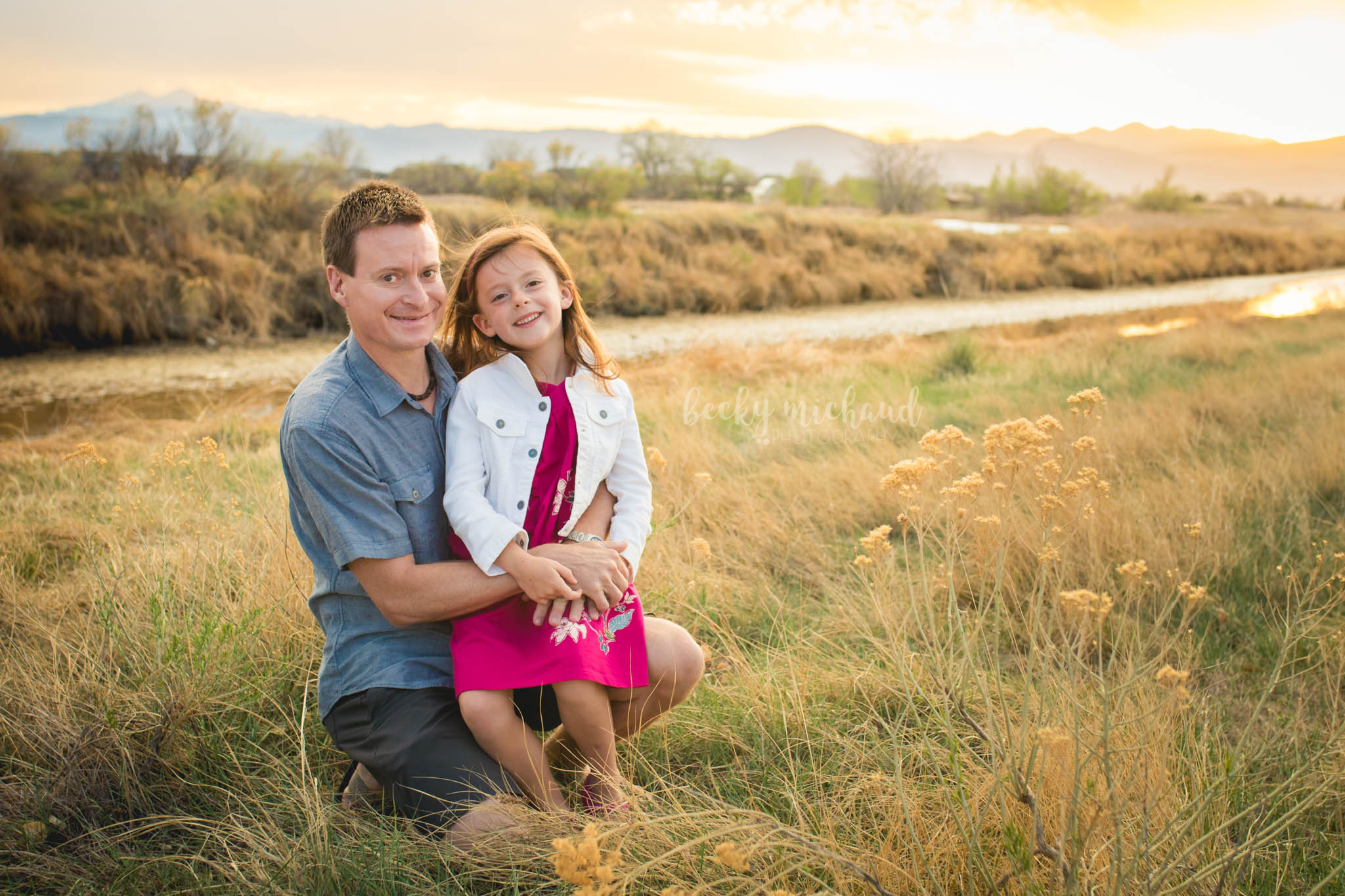 a father and his daughter pose in a field in front of the mountains  for their photo session in Loveland, Colorado