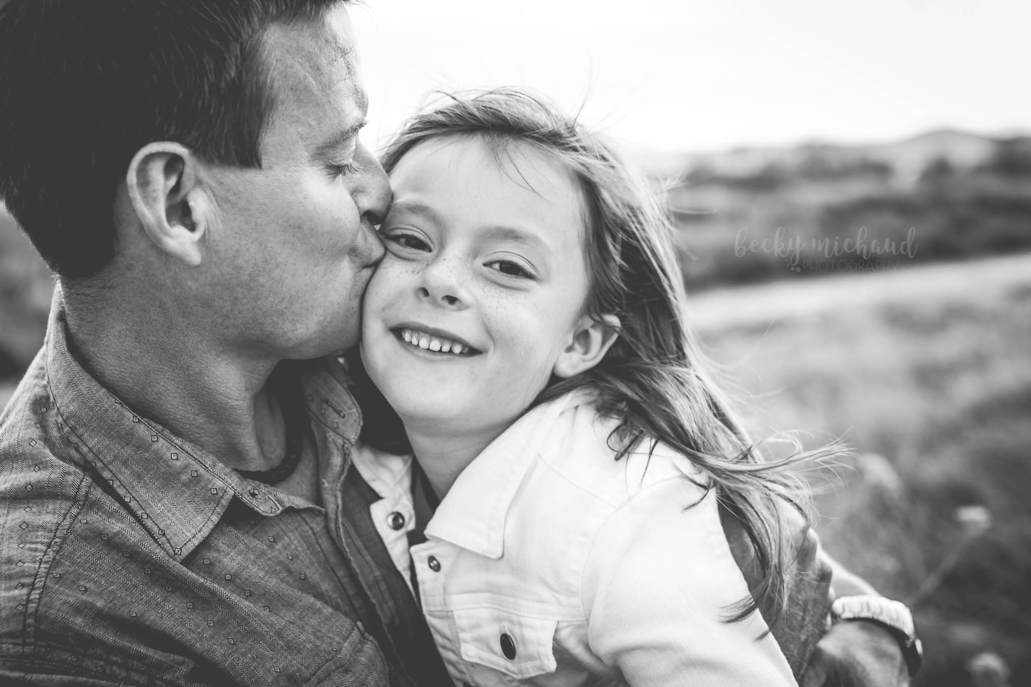 black and white photo of a dad kissing his daughter taken by Becky Michaud, Northern Colorado photographer