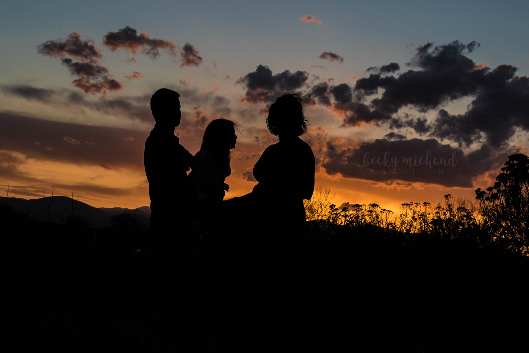 silhouette of a family of three at sunset over Equalizer Lake in Loveland, Colorado
