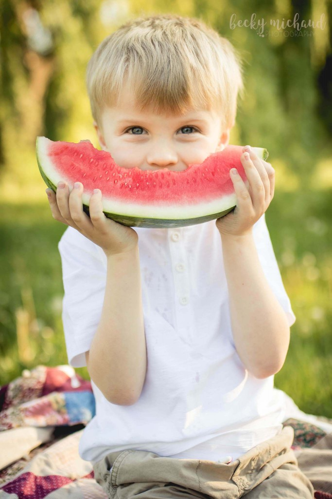 little boy smiling with a giant slice of watermelon