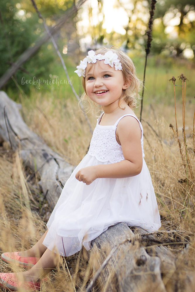Sweet two year old girl in a white dress with a white flower crown poses for her milestone photo session in Fort Collins, Colorado