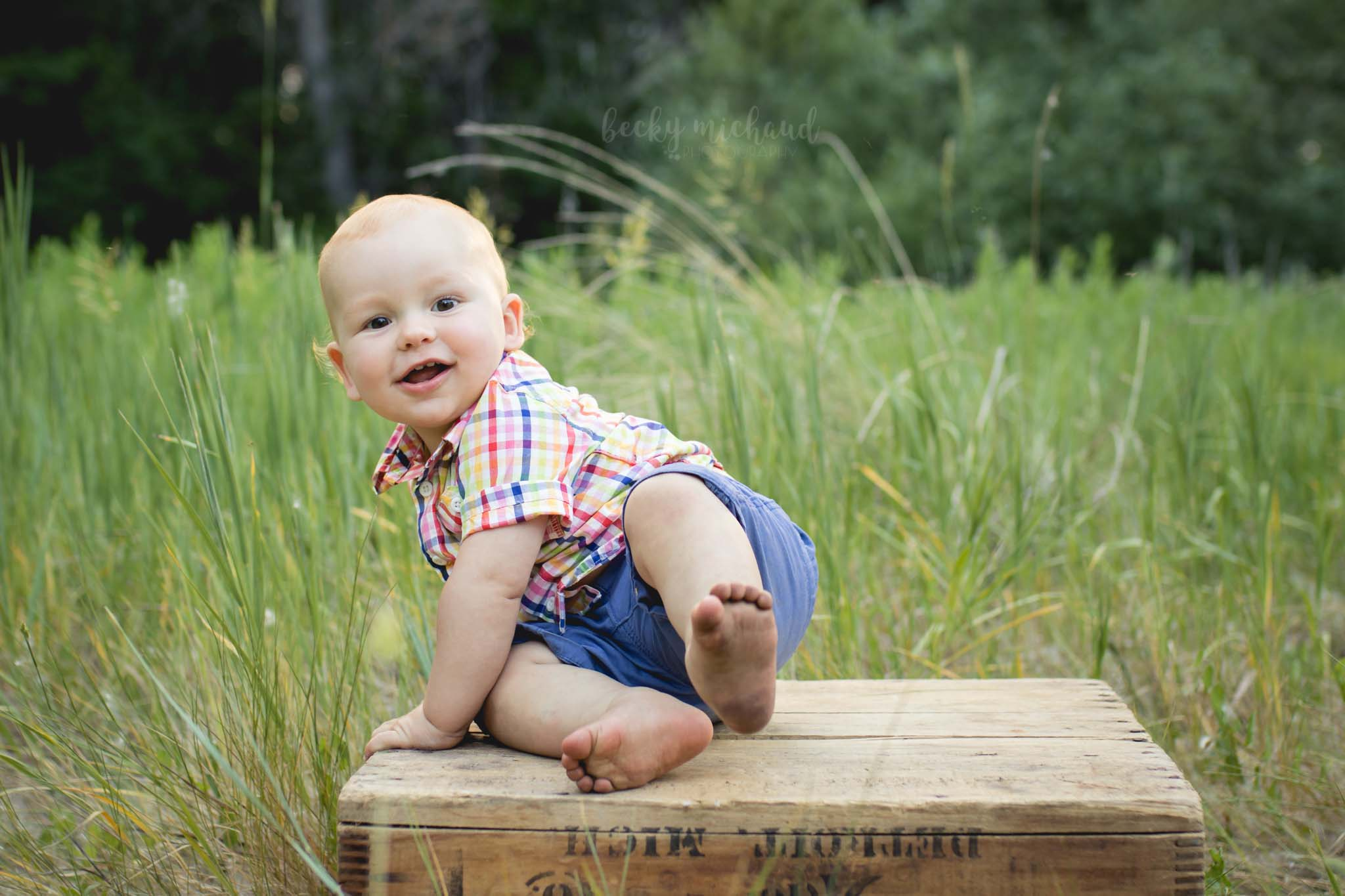 baby boy plays on an antique shipping crate