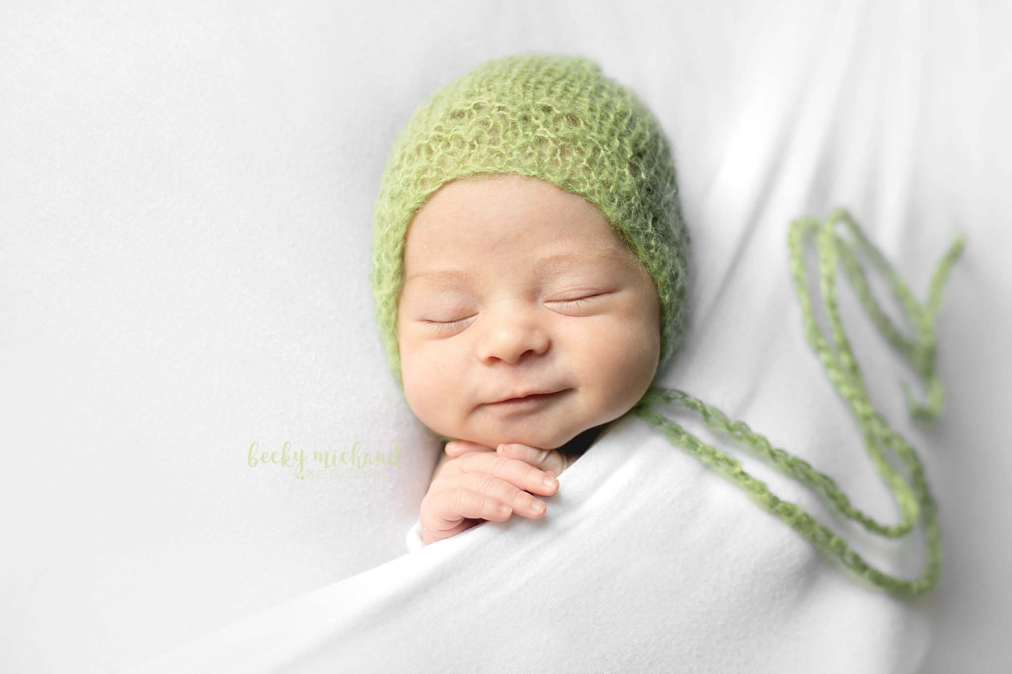 Baby girl wearing a green bonnet in a simple newborn portrait