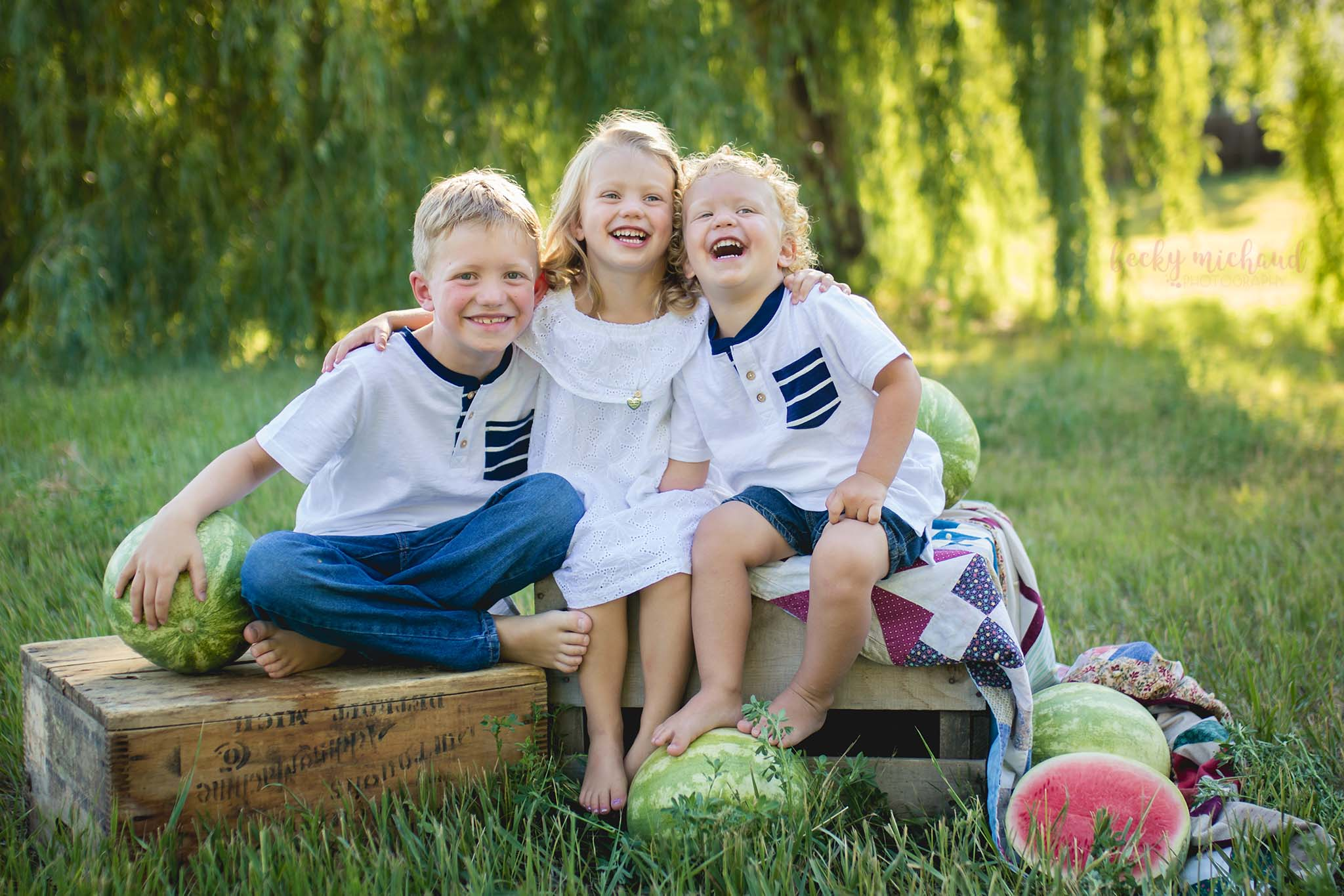 Three siblings laughing together during their watermelon mini session photo shoot
