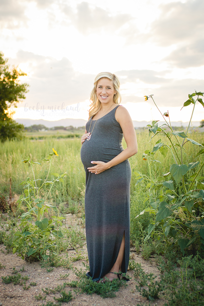 Photo of a mother to be posing for her maternity session in a field with sunflowers