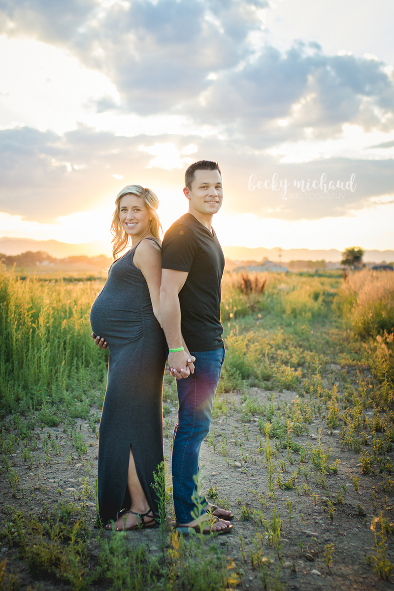 pregnancy portrait of a couple in a field in Fort Collins Colorado near sunset
