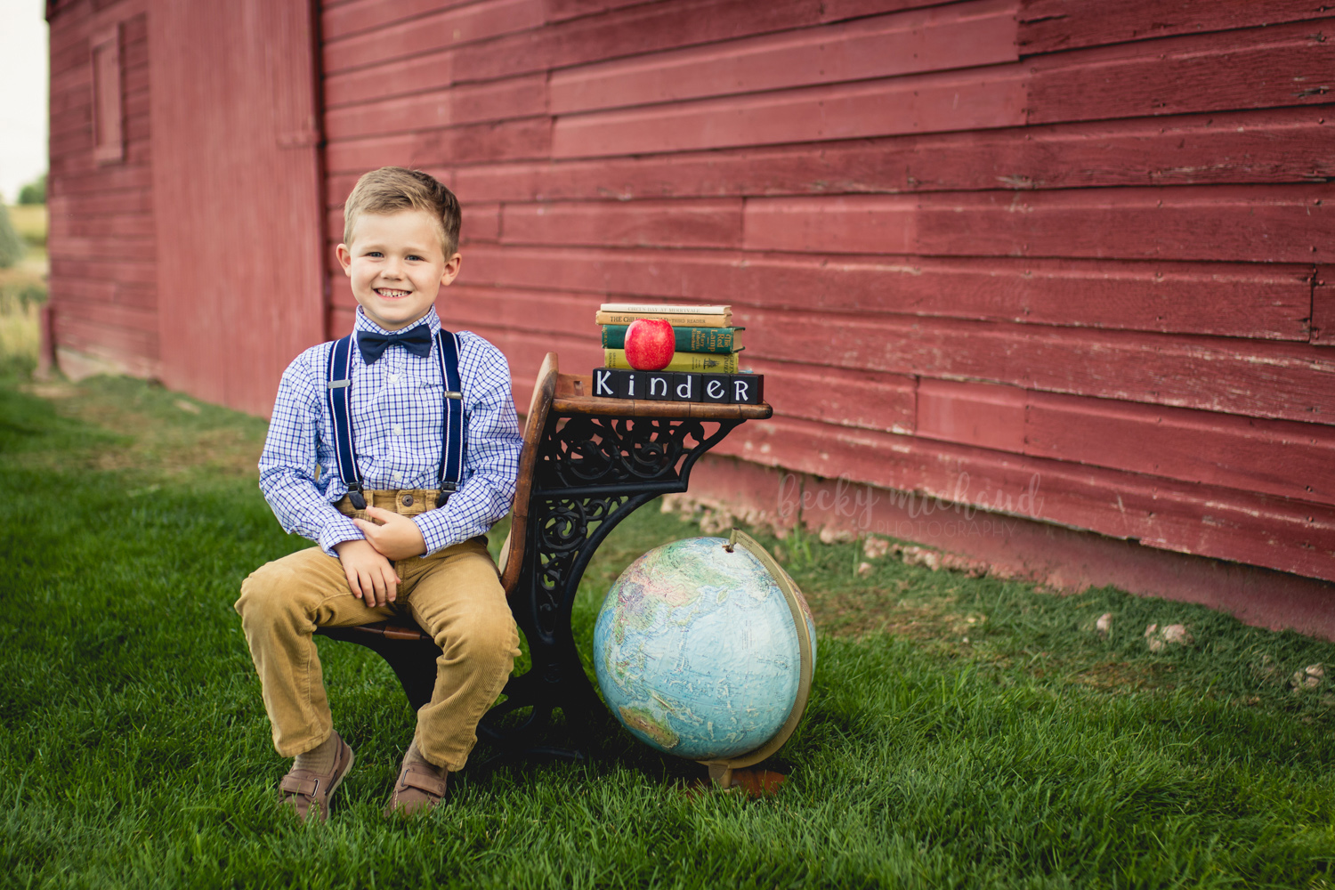 A boy poses on an antique desk for his back to school mini session