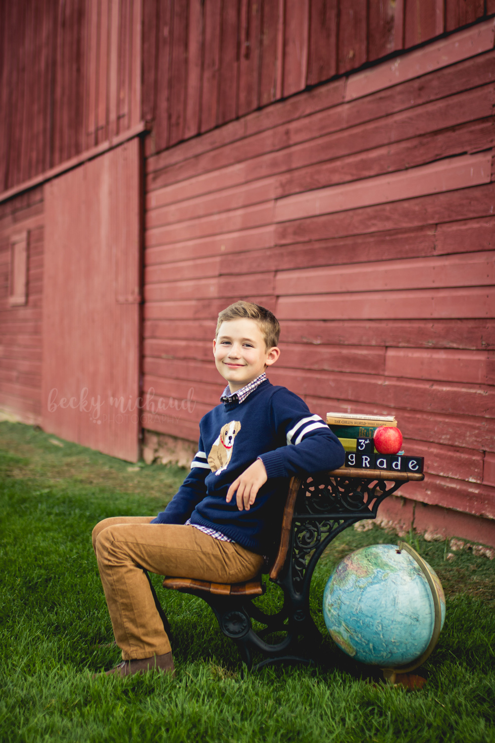 A boy poses for his back to school mini session by a red barn in Fort Collins, Colorado
