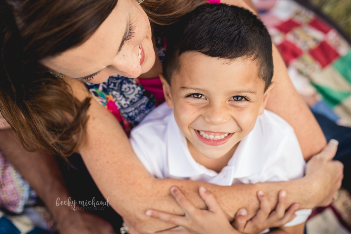 A boy cuddles with his mom during their family photo session at Dixon Reservoir in Fort Collins