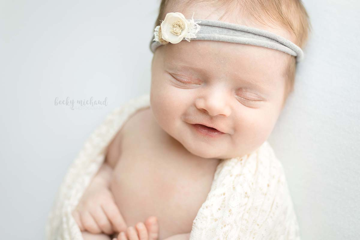 Baby smiling and wearing a headband by Edna Magdalene