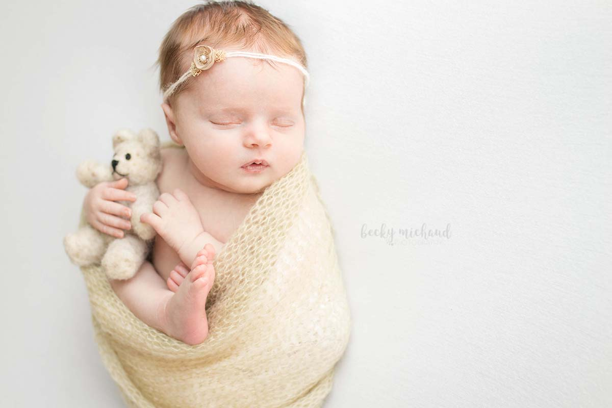 newborn girl wearing a simple headband by Edna Magdalene and holding a felted wool bear