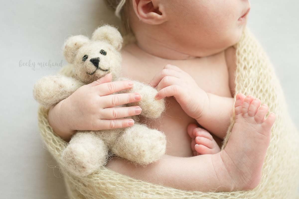 felted wool teddy bear being held by a newborn baby
