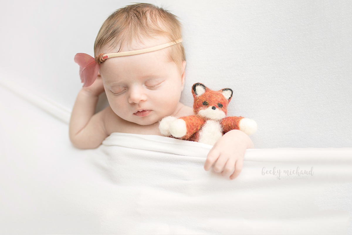 Baby girl with a felted wool fox and pink feather headband