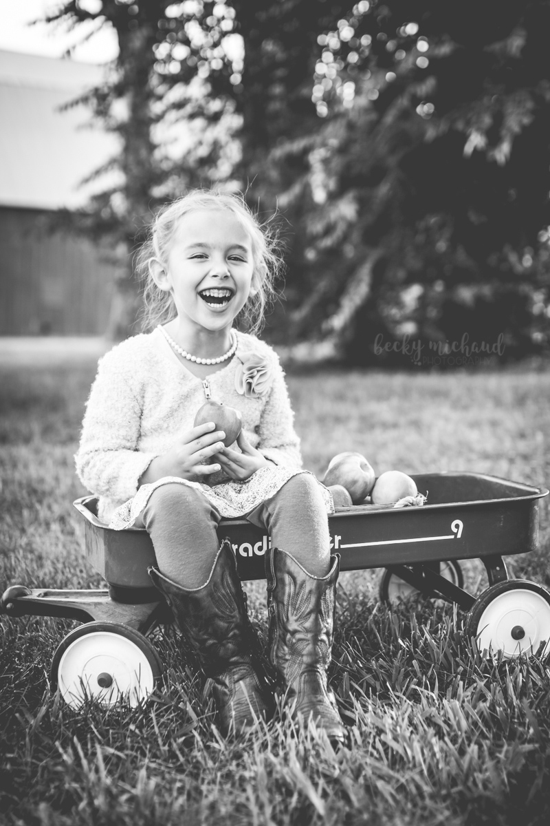 Black and white fall photo of a girl laughing