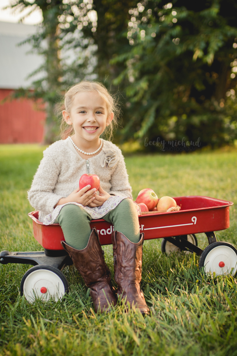 A girl holds and apple in a wagon by a red barn