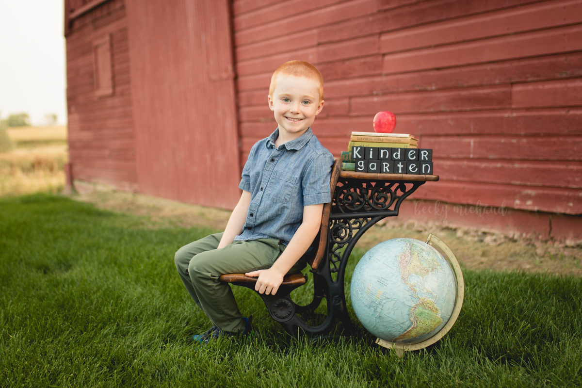A child poses on an antique desk for his back to school photo session
