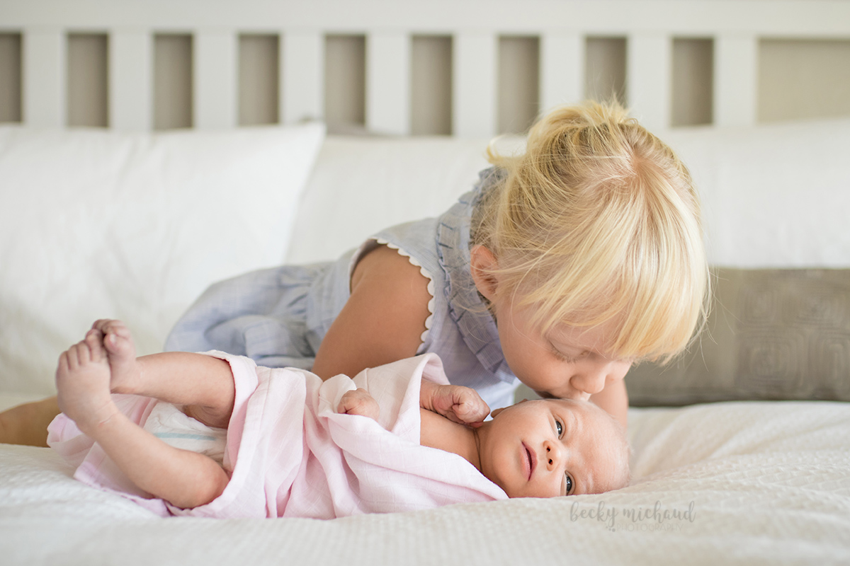 A little girl kisses her baby sister on the head during their in home lifestyle photo session