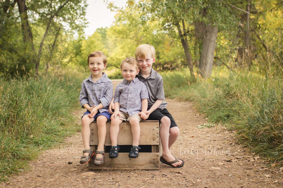 Three brothers sit on a crate on a dirt path during their photo session at Fort Collins Legacy Park