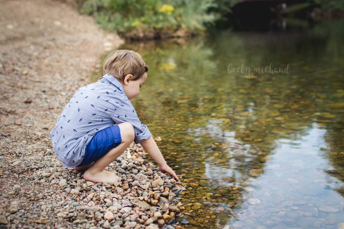 A little boy reaches down to touch the Poudre River during his family photo session