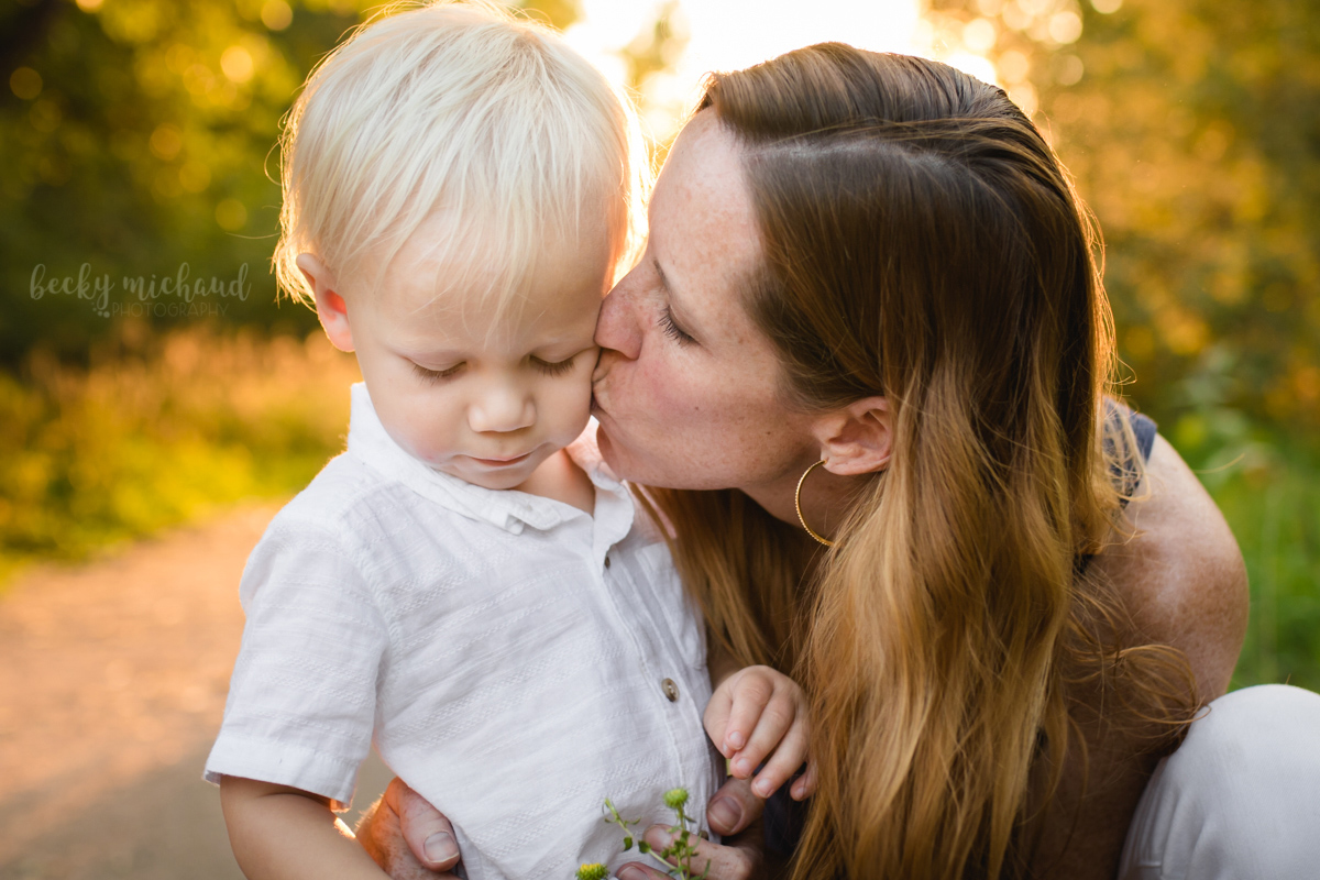 A little boy gets a kiss from his mom during their Fort Collins family photo session with Becky Michaud