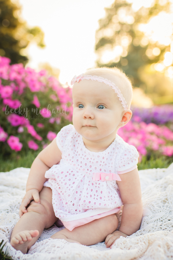 A 6 month old girl sits on a blanket at the flower garden on CSU campus in Fort Collins, CO
