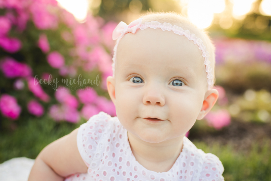 A baby girl smiles for the camera during her Fort Collins photo session