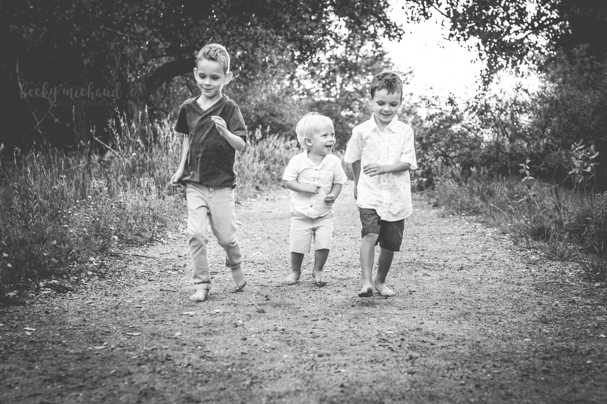 Black and white photo of three brothers running down a path in a natural area in Fort Collins, Colorado