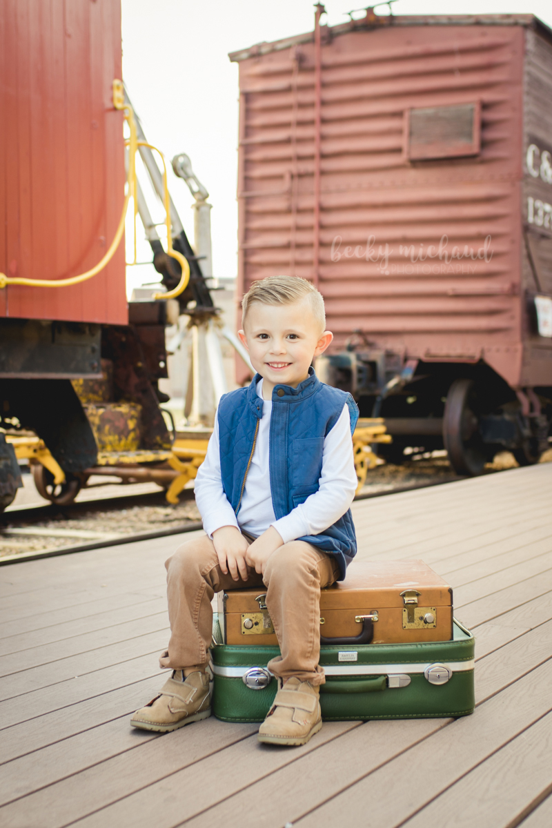 A little boy sits on some vintage suitcases in front of the train cars at Boardwalk Park in Windsor Colorado