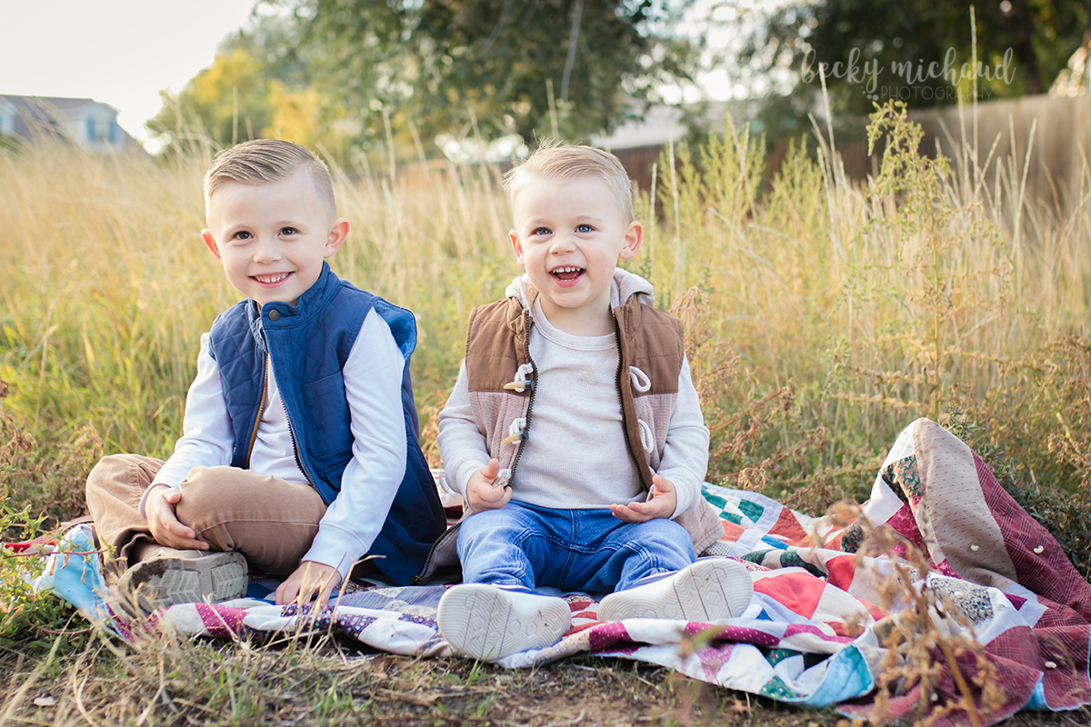 Two brothers sit on a blanket together for their photo session in Windsor, Colorado