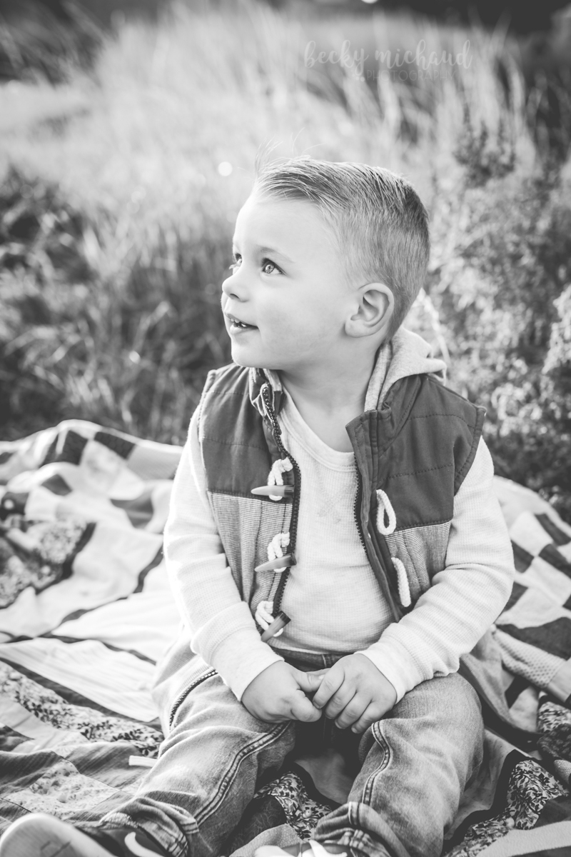 black and white portrait of a toddler looking up and smiling at Boardwalk Park in Windsor, Colorado