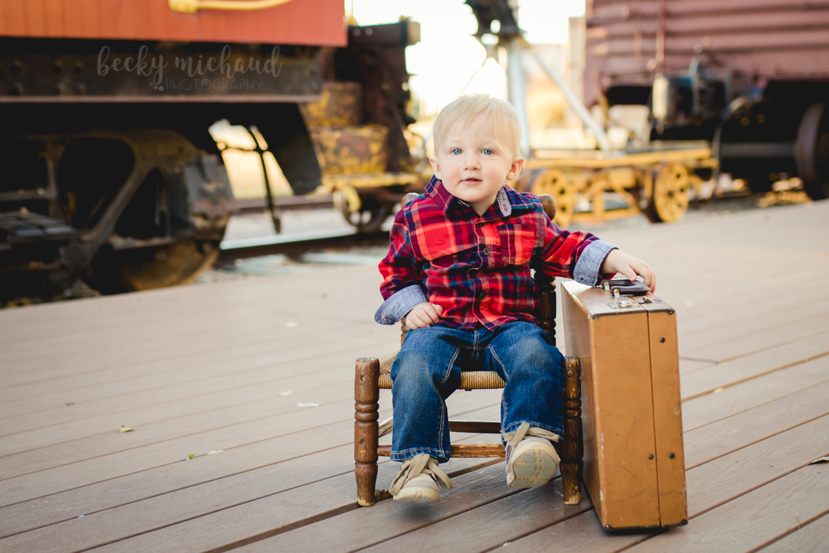 One year old boy sitting on a little chair with a suitcase at the Windsor Train Museum